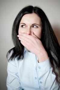 embarrassed woman covers her smile