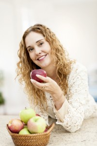 pretty lady smiling holding an apple