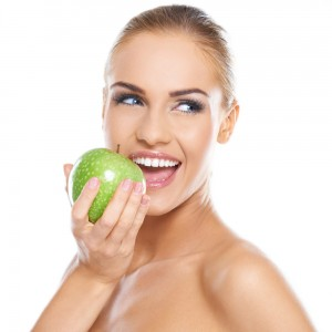 woman with bright smile eating an apple